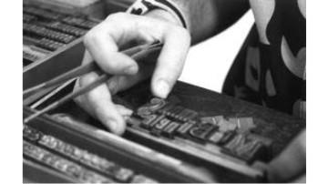 Tipógrafo montando chapa com tipos móveis